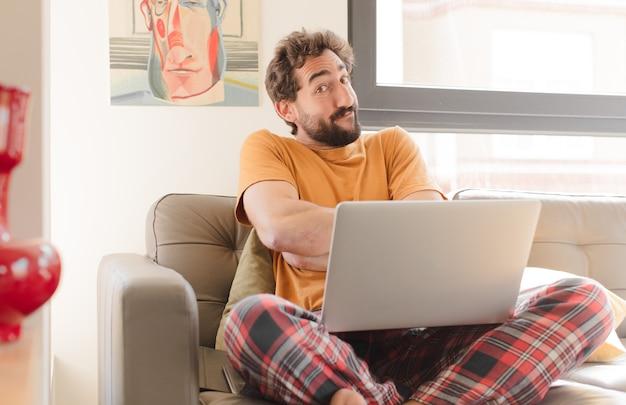Jovem barbudo encolhendo os ombros sentindo-se confuso e incerto, duvidando com os braços cruzados e olhar perplexo sentado com um laptop