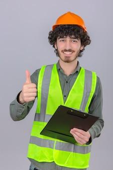Jovem barbudo engenheiro bonito usando capacete de segurança e colete com sorriso no rosto, aparecendo o polegar sobre parede branca isolada