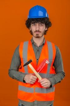 Jovem barbudo engenheiro bonito usando capacete de segurança e colete segurando a chave ajustável e martelo com rosto sério em pé sobre a parede laranja isolada