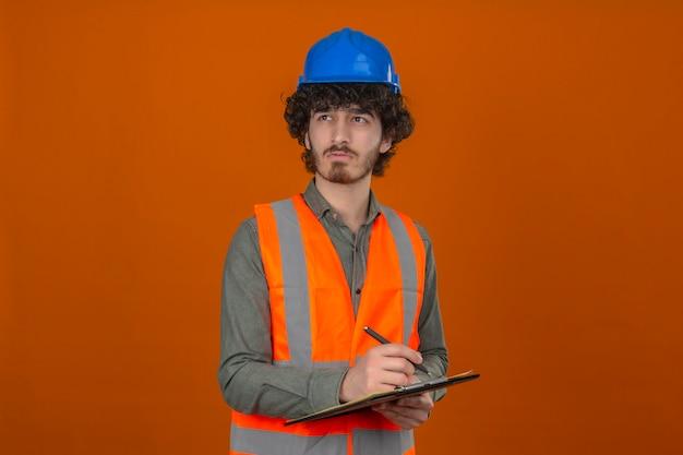 Jovem barbudo engenheiro bonito usando colete de construção e capacete de segurança segurando a prancheta escrevendo algo olhando de lado expressão pensativa no rosto sobre parede laranja isolada