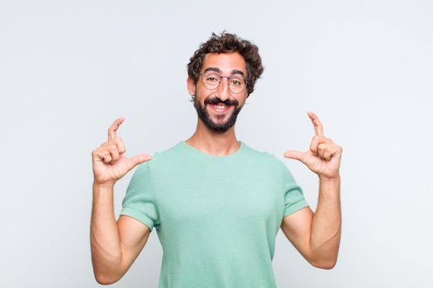 Jovem barbudo enquadrando ou esboçando o próprio sorriso com as duas mãos, parecendo positivo e feliz, conceito de bem-estar