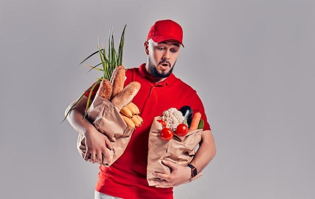 Jovem barbudo entregador de uniforme vermelho contém dois grandes pacotes pesados com pão e vegetais isolados no fundo cinza.