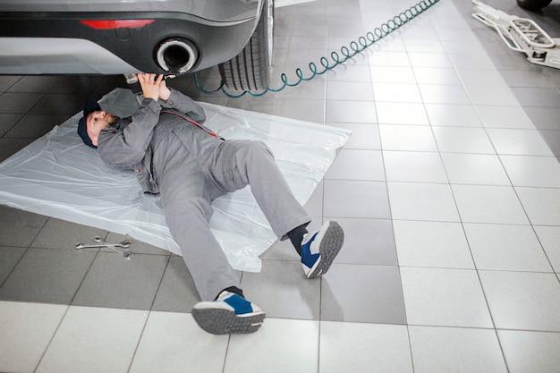 Jovem barbudo está deitado debaixo do carro e mantém o tubo longo com as mãos. ele é sério e concentrado. o homem trabalha.
