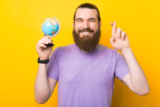 Jovem barbudo está segurando um pequeno globo e cruzando os dedos.