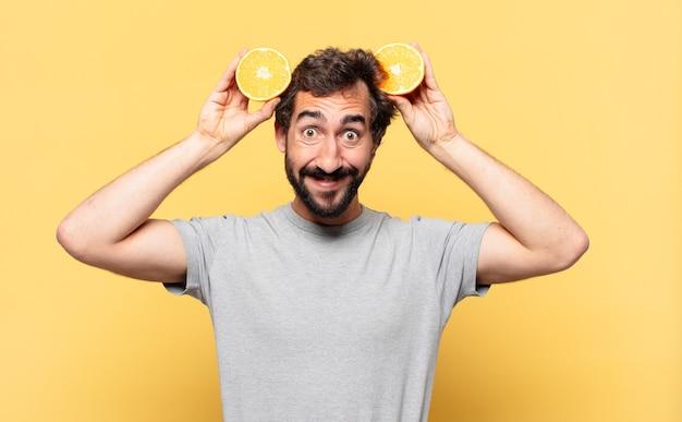 Jovem barbudo fazendo dieta e expressão feliz e segurando uma laranja