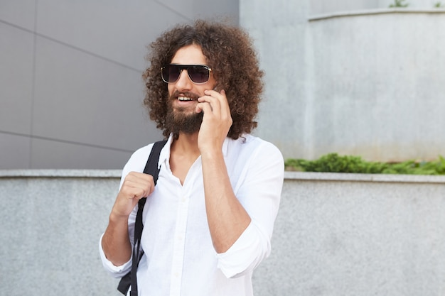 Jovem barbudo feliz andando pela rua e falando ao telefone, usando óculos escuros e roupas casuais, sendo alegre e satisfeito