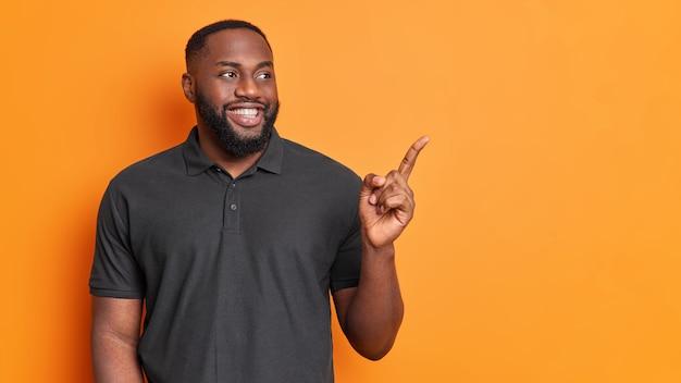 Jovem barbudo feliz aponta para a direita com o dedo indicador mostra um espaço de cópia incrível contra a parede laranja do estúdio vestido casualmente sugere uma boa oferta