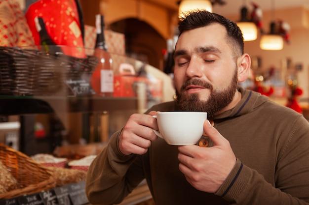 Jovem barbudo feliz apreciando o cheiro de café fresco, tomando café da manhã no café, copie o espaço