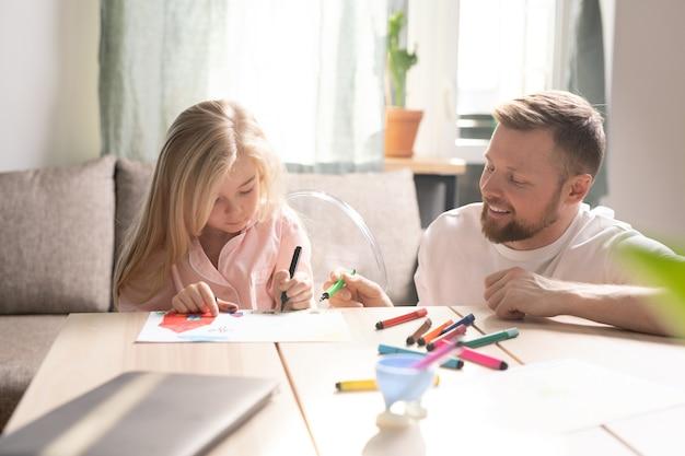 Jovem barbudo feliz com um marcador verde apontando para o papel enquanto sua filhinha desenha com lápis de cor