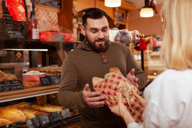 Jovem barbudo feliz comprando um delicioso pão fresco no padeiro
