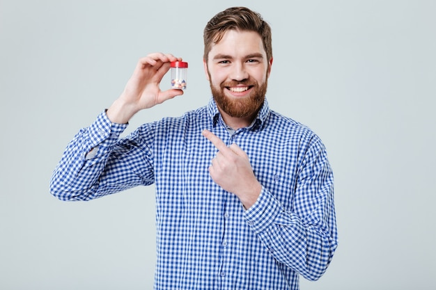 Jovem barbudo feliz segurando e apontando no frasco de comprimidos na parede branca