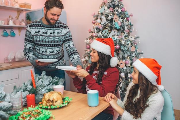 Jovem barbudo fica e dá pratos para mulher. ele sorri. mulher pegá-los. eles se sentam à mesa com copos nas mãos e olham para o homem. as meninas usam chapéus vermelhos.