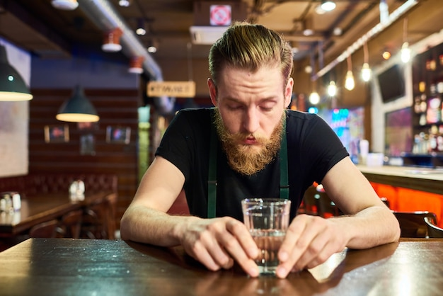 Jovem barbudo, ficando bêbado no bar