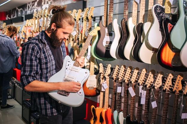 Jovem barbudo ficar e tocar violão. ele segura nas mãos. há outras guitarras elétricas penduradas na parede.