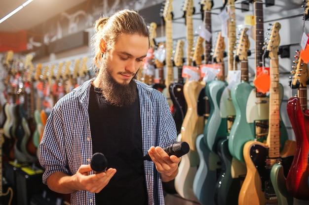 Jovem barbudo ficar perto de guitarras elétricas na sala. ele segura dois microfones pretos nas mãos. cara olha para eles. ele está concentrado.
