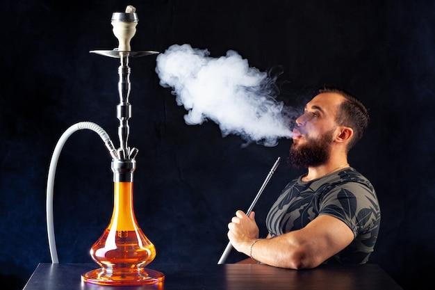 Jovem barbudo fumando shisha em uma boate escura perto