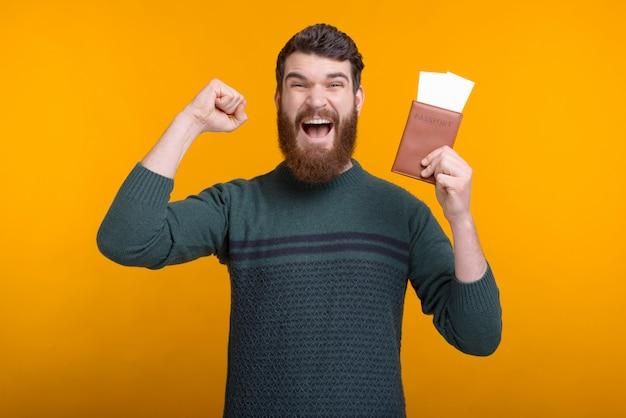 Jovem barbudo ganhou uma viagem para dois está fazendo gesto vencedor, mantendo um passaporte e bilhetes.