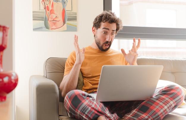 Jovem barbudo gritando com as mãos para o alto, sentindo-se furioso, frustrado, estressado e chateado, sentado com um laptop