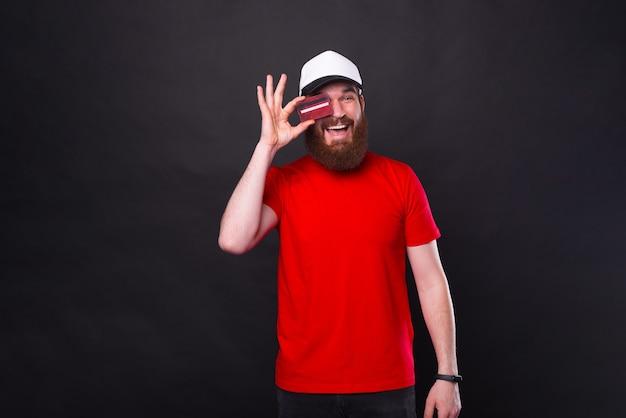 Jovem barbudo hippie alegre vestindo uma camiseta vermelha e segurando um cartão de crédito vermelho sobre os olhos