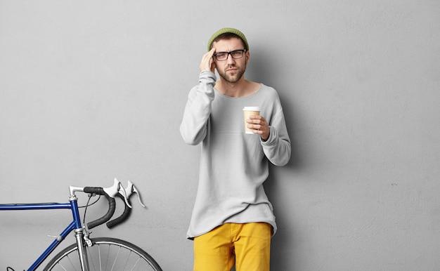 Jovem barbudo hipster europeu de chapéu e óculos, bebendo café em copo de papel descartável e tocando o templo enquanto sofre de dor de cabeça de enxaqueca, tendo dia estressante