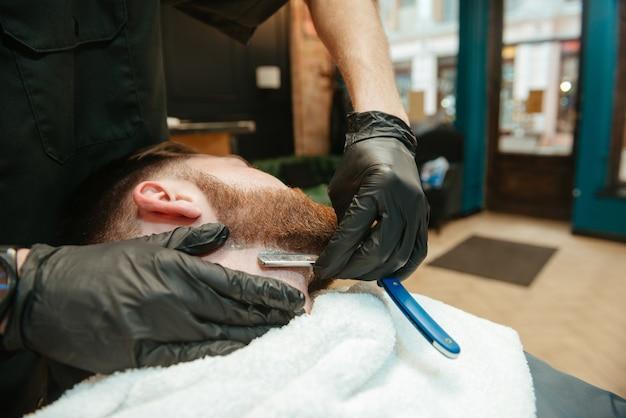 Jovem barbudo homem barbear-se barbear por cabeleireiro enquanto está na cadeira de barbearia.