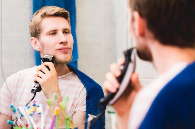 Jovem barbudo homem bonito com barba com máquina no banheiro olhando no espelho