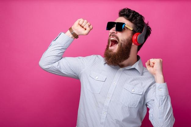 Jovem barbudo homem cantando, dançando e ouvindo a música em fundo rosa.
