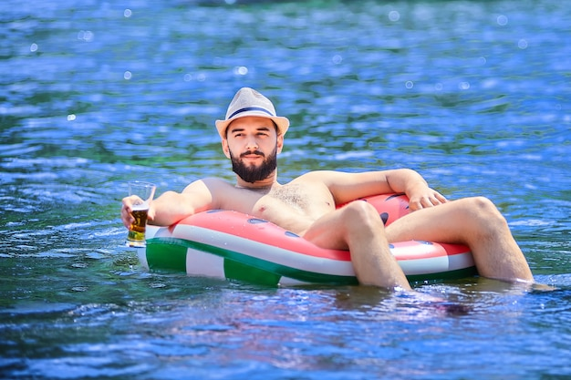 Jovem barbudo homem caucasiano com chapéu relaxando no anel de borracha na água com um copo de cerveja na mão
