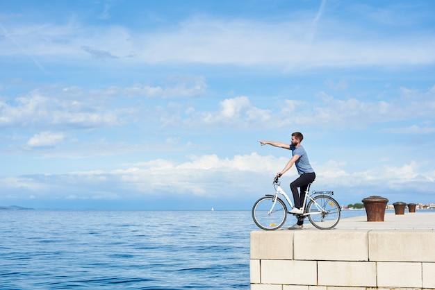 Jovem barbudo homem de bicicleta na calçada de pedra pavimentada alta apontando para montanha distante na costa oposta na água do mar azul claro e fundo pequeno barco à vela