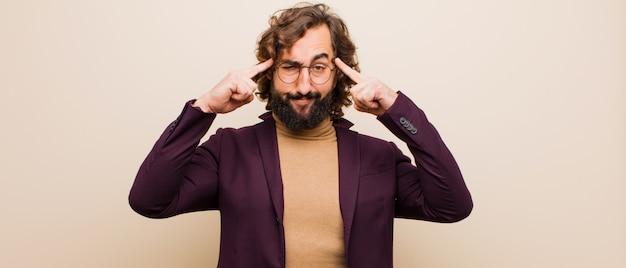 Jovem barbudo homem louco com um olhar sério e concentrado, de brainstorming e pensando em um problema desafiador contra a cor lisa