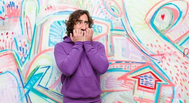Jovem barbudo homem louco olhando preocupado, ansioso, estressado e com medo, roer unhas e olhando para copyspace lateral contra grafite