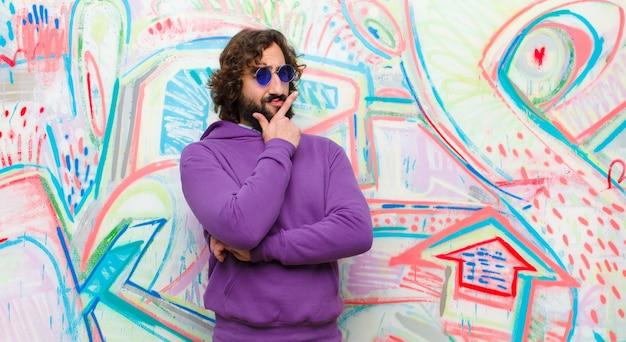 Jovem barbudo homem louco olhando sério, pensativo e desconfiado, com um braço cruzado e mão no queixo, opções de pesagem contra parede grafite