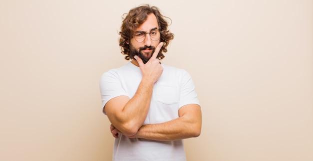 Jovem barbudo homem louco olhando sério, pensativo e desconfiado, com um braço cruzado e mão no queixo, opções de ponderação