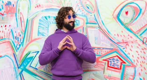 Jovem barbudo homem louco planejando e conspirando, pensando em truques e truques desonestos, astúcia e traição na parede do graffiti