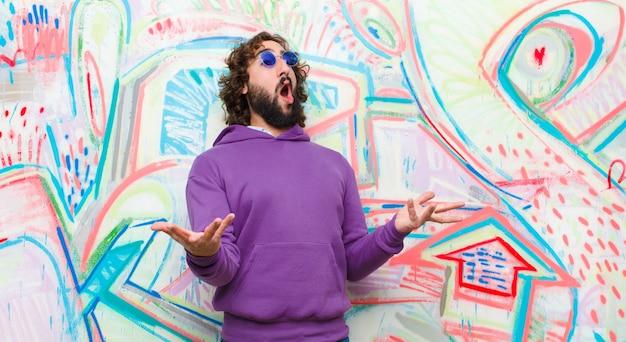 Jovem barbudo homem louco realizando ópera ou cantando em um concerto ou show, sentindo-se romântico, artístico e apaixonado contra a parede de graffiti