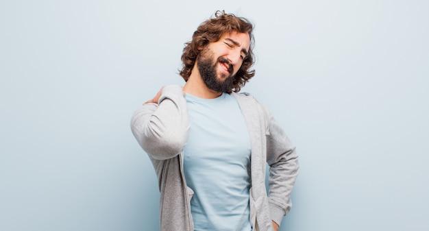 Jovem barbudo homem louco se sentindo cansado, estressado, ansioso, frustrado e deprimido, sofrendo com dores nas costas ou no pescoço
