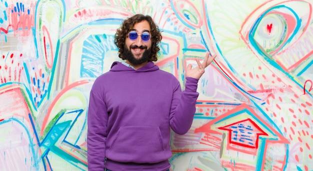 Jovem barbudo homem louco se sentindo feliz, surpreso e alegre, sorrindo com atitude positiva, percebendo uma solução ou idéia na parede de graffiti