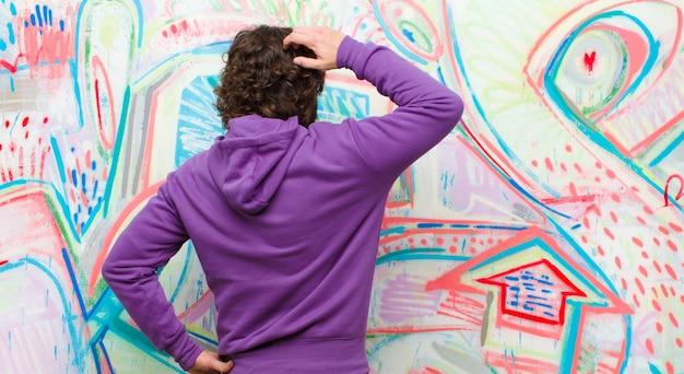 Jovem barbudo homem louco se sentindo sem noção e confuso, pensando uma solução, com a mão no quadril e outro na cabeça, vista traseira na parede do graffiti