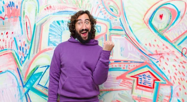 Jovem barbudo homem louco sentindo chocado, animado e feliz, rindo e comemorando o sucesso, dizendo uau! na parede de graffiti