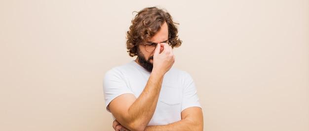 Jovem barbudo homem louco sentindo estressado, infeliz e frustrado, tocando a testa e sofrendo de enxaqueca de dor de cabeça severa contra parede rosa