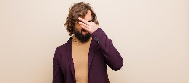 Jovem barbudo homem louco sentindo nojo, segurando o nariz para evitar cheirar um fedor sujo e desagradável contra cor lisa
