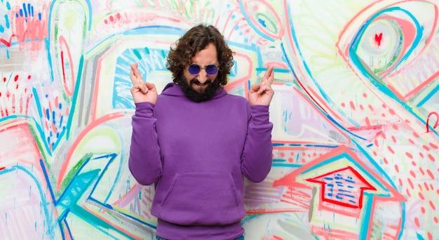 Jovem barbudo homem louco, sentindo-se nervoso e esperançoso, cruzando os dedos, rezando e esperando por boa sorte contra a parede do graffiti