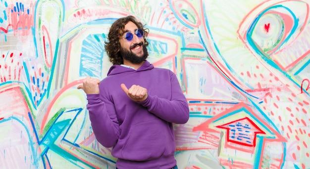 Jovem barbudo homem louco sorrindo alegremente e casualmente apontando para copiar o espaço ao lado, sentindo-se feliz e satisfeito na parede de graffiti