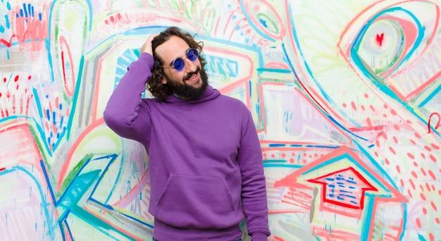 Jovem barbudo homem louco sorrindo alegremente e casualmente, levando a mão à cabeça com um olhar positivo, feliz e confiante na parede de graffiti