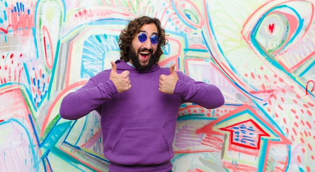 Jovem barbudo homem louco sorrindo amplamente olhando feliz, positivo, confiante e bem sucedido, com os dois polegares contra a parede do graffiti