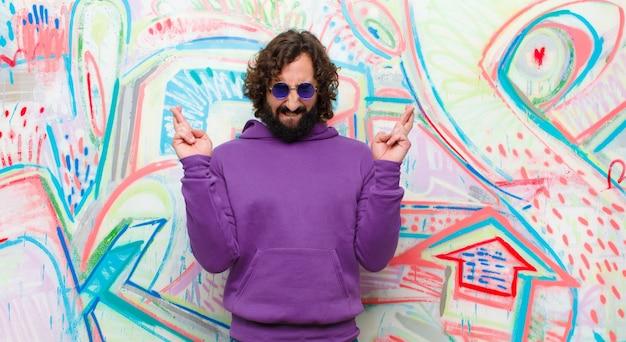 Jovem barbudo homem louco sorrindo e cruzando ansiosamente os dois dedos, sentindo-se preocupado e desejando ou esperando boa sorte contra a parede do graffiti