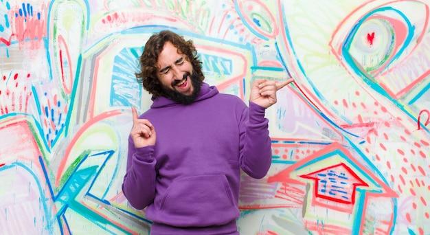 Jovem barbudo homem louco sorrindo, sentindo-se despreocupado, relaxado e feliz, dançando e ouvindo música, se divertindo em uma festa contra grafite