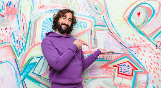 Jovem barbudo homem louco sorrindo, sentindo-se feliz, despreocupado e satisfeito, apontando para o conceito ou idéia no espaço da cópia do lado na parede de grafite