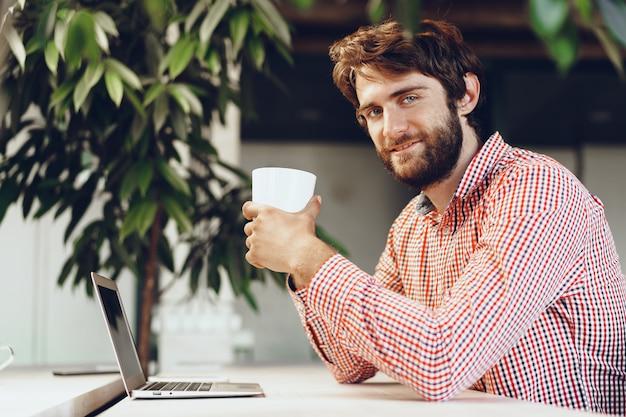 Jovem barbudo homem vestindo camisa casual, usando seu computador laptop. retrato de empresário