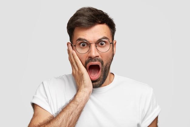Jovem barbudo irritado parece muito surpreso, abre a boca amplamente, toca a bochecha com a palma da mão